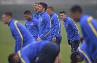 Arsenal's Mesut Ozil (3rd R) stretches during a training session at London Colney near Lon