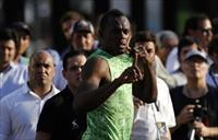Jamaican sprinter Usain Bolt gestures before competing in a race against a public bus duri