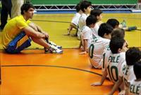 U.S. swimmer Michael Phelps (L) sits behind children during a promotional event in Sao Pau