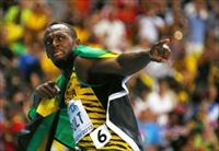Usain Bolt of Jamaica poses with his national flag after winning the men's 100 metres fina