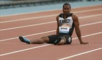 Yohan Blake of Jamaica sits on the track after falling in the men's 100m during the IAAF D