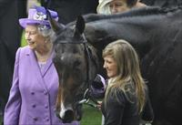 Britain's Queen Elizabeth (L) smiles as she stands with her horse Estimate after it won th