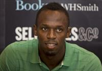 Jamaican athlete Usain Bolt poses for photographers as he signs copies of his autobiograph