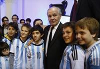 Argentina's national soccer team coach Alejandro Sabella poses for a picture with children