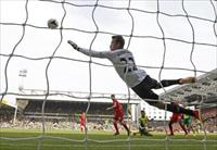Robert Snodgrass (C) heads and scores his goal past Liverpool goalkeeper Simon Mignolet (t