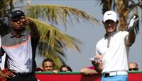 Tiger Woods of the U.S. and Rory McIlroy of Northern Ireland gesture as they prepare to ta