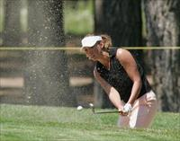 Olympic Gold Medalist swimmer Amy Van Dyken hits out of a bunker on the 15th green during
