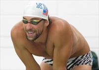Michael Phelps stands on the edge of the warm up pool during the Arena Grand Prix at Meckl