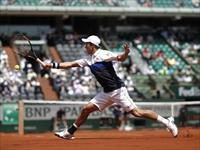 Kei Nishikori of Japan plays a shot to Thomaz Bellucci of Brazil during their men's single