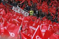 Manchester United fans wave flags before the English Premier League soccer match against S