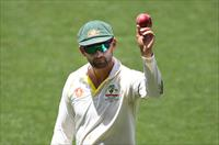 Australia's Nathan Lyon shows the ball as he leaves the field following his 6 wicket haul