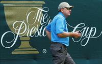 FILE PHOTO: International Team captain Nick Price of Zimbabwe carries a two-way radio duri
