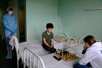 Chess players from France look at the board during a game at a hospital in Murmansk, Russi