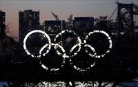 The giant Olympic rings are seen  in the dusk through a tree at the waterfront area at Oda
